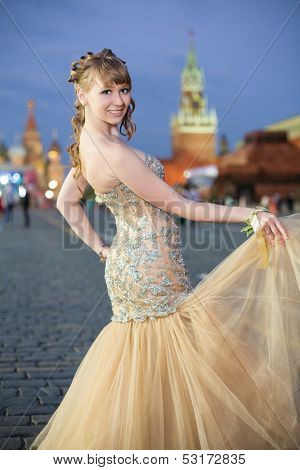 A smiling girl in a beautiful dress on Red Square near the Kremlin