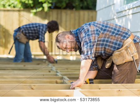 Side view of mid adult carpenters working at construction site