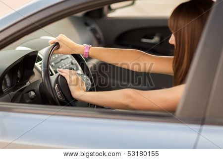 transportation and vehicle concept - woman driving a car with hand on horn button poster