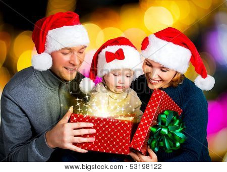 Happy Familiy With One Baby Opens The  Box With Christmas Gifts