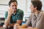 Two friendly male mature students chatting while sitting in class room poster