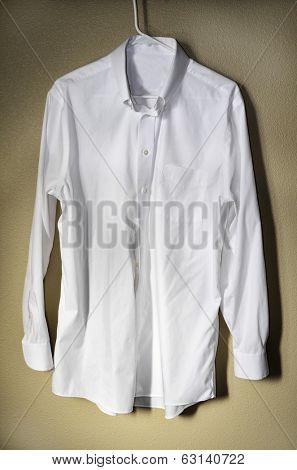 Detail of white dress shirt hanging on hanger with light