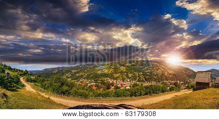 Village On Hillside Of Mountain At Sunset