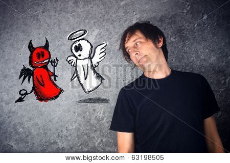 Casual Man Looking At Doodle Drawing Of Angel And Devil Fighting.
