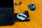 The laptop is loaded with a DVD drive on table background,laptop with cd case open on the table poster