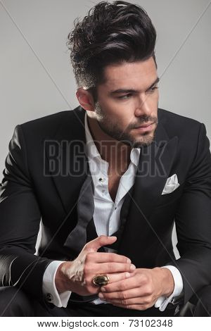 Close up picture of a serious young man in tuxedo, looking away from the camera, thinking.