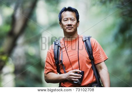 Portrait of man holding binoculars while hiking