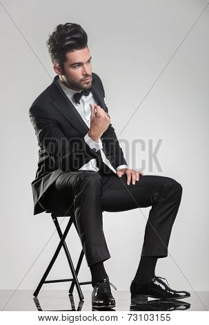 Elegant young man in tuxedo sitting on a stool while snapping his finger, looking away from the camera.
