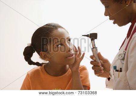Female doctor looking inside patient's ear