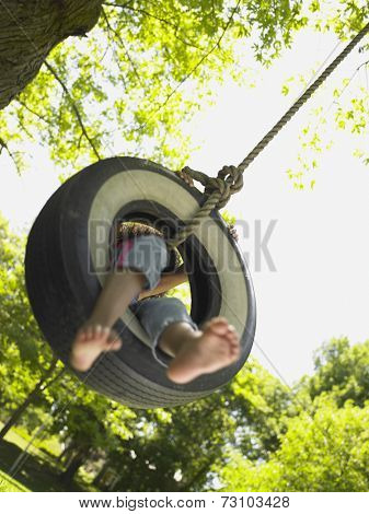 Barefoot girl on tire swing