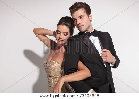 Woman wearing elegant dress holding her lover arm, looking down, while the man is ajusting his jacket.