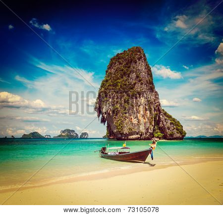 Vintage retro effect filtered hipster style travel image of long tail boat on tropical beach with limestone rock, Krabi, Thailand