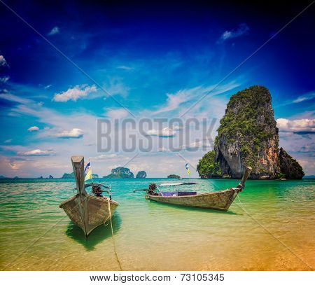 Vintage retro effect filtered hipster style travel image of long tail boats on tropical beach (Pranang beach), Krabi, Thailand
