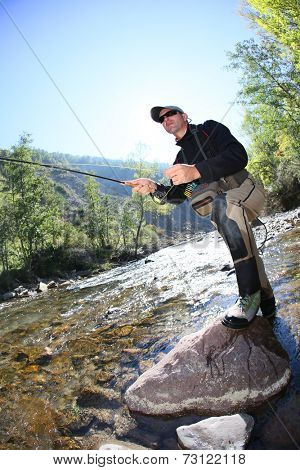 Fly fisherman using flyfishing rod in beautiful river