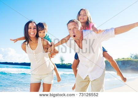 Happy Mixed Race Family of Four Playing on the Beach