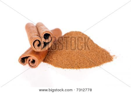 Cinnamon powder and sticks isolated on white
