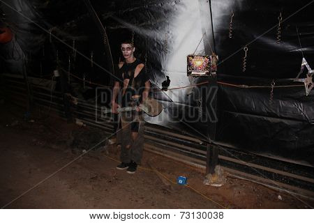 MUSKOGEE, OK - Sept. 13: Scary zombies hide in the tunnel and attack unsuspecting athletes as they race during the Castle Zombie Run at the Castle of Muskogee in Muskogee, OK on September 13, 2014.