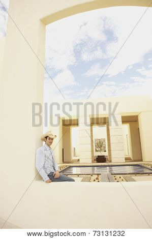 Man sitting next to luxury hotel pool