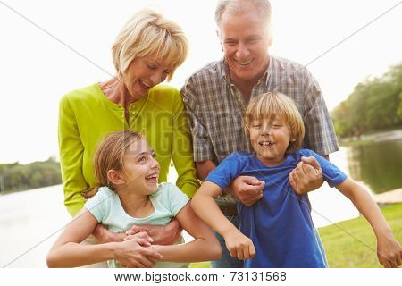 Grandparents Playing With Grandchildren Outdoors