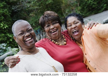 Three middle-aged African women smiling and hugging