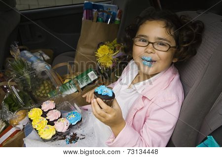 Girl sitting in backseat of car eating with groceries