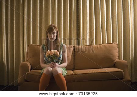 Woman sitting on sofa with bouquet of flowers