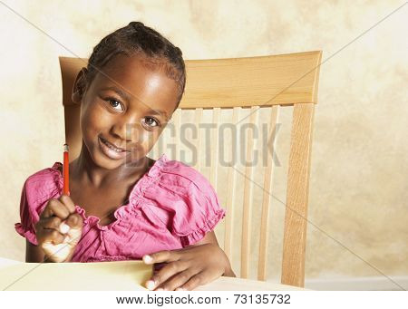 Young African girl holding pencil and smiling