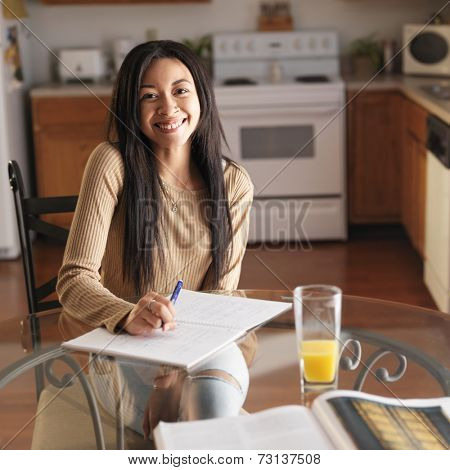 teen girl at home studying and smiling