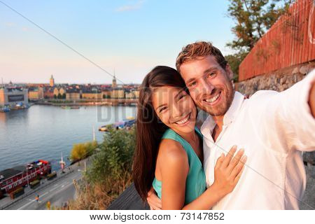 Couple taking selfie self portrait in Stockholm. Candid fresh Scandinavian man and Asian woman looking at old town cityscape sunset view from Monteliusvagen overlooking Gamla Stan, the old town.