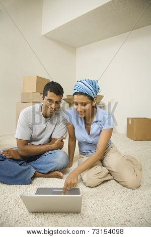 Indian couple looking at laptop in new house
