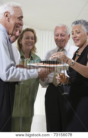 Group of seniors at party eating hors d'oeuvres