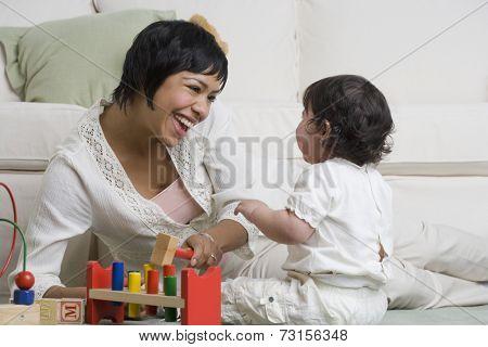Hispanic mother and baby playing on floor