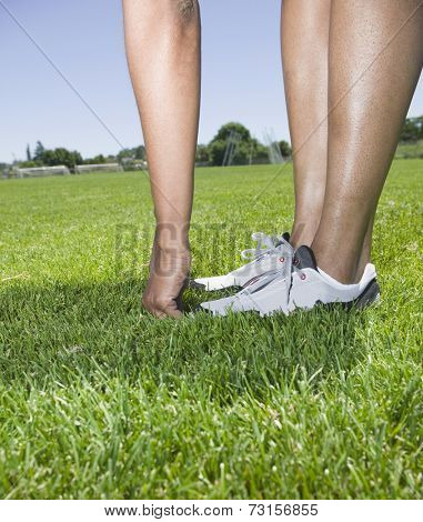 African person touching toes in grass