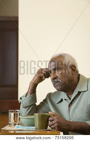 Senior African man at breakfast table