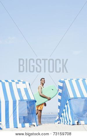 Hispanic man holding boogie board at beach