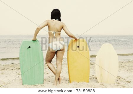 Young woman leaning on boogie boards at beach