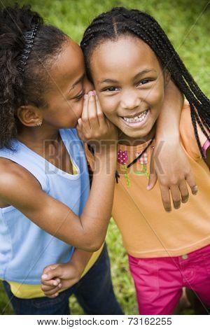 Portrait of African girls telling secret