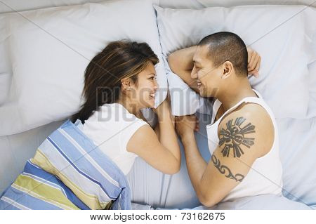 Asian couple smiling at each other in bed