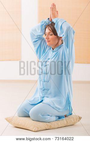 Beautiful woman meditating wearing professinal, oryginal chinese clothes at gym