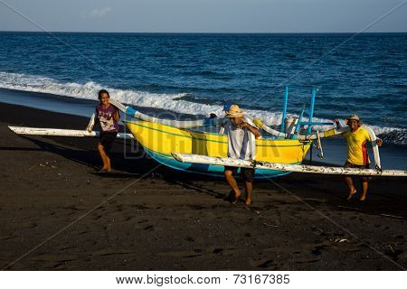 SEPTEMBER 18, 2014 - BALI, INDONESIA: Balinese fishermen return from sea after a fishing trip out into the ocean.  Deep sea fishing using traditional outrigger boats is still a common practice here.