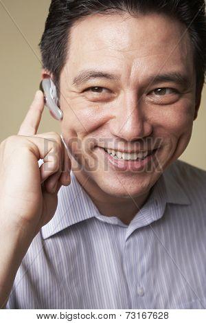 Asian man wearing hands free device