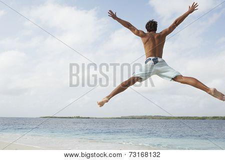 South American man jumping on beach