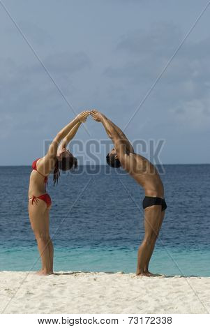 Multi-ethnic couple practicing yoga at beach