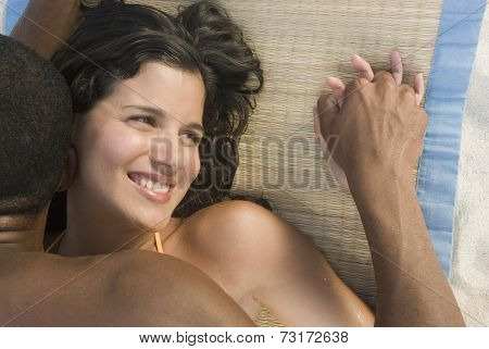 Hispanic couple laying on beach mat