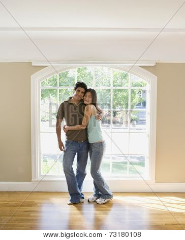 Multi-ethnic couple hugging in new house