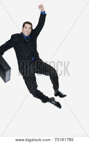 Hispanic businessman clicking heels in air