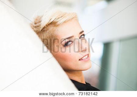 smiling young blue eyes woman with short blonde hair outdoor city portrait