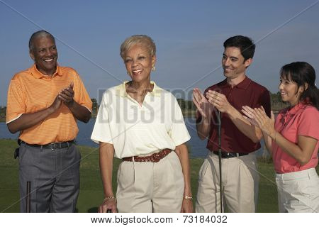 Multi-ethnic friends clapper for senior woman on golf course
