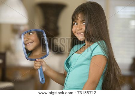 Hispanic girl holding mirror