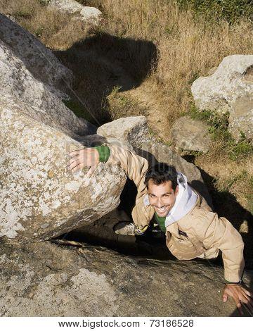 Pacific Islander man climbing rock formation